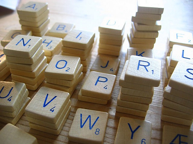 Stacks of white Scrabble tiles, with blue letters