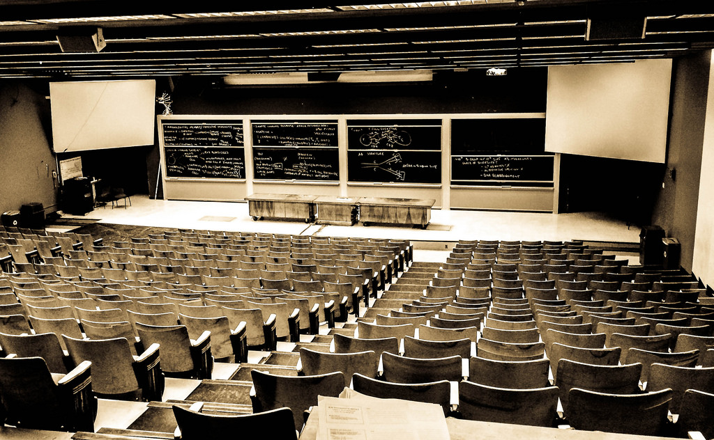 Sepia-tone photograph taken from the back of a large empty lecture hall