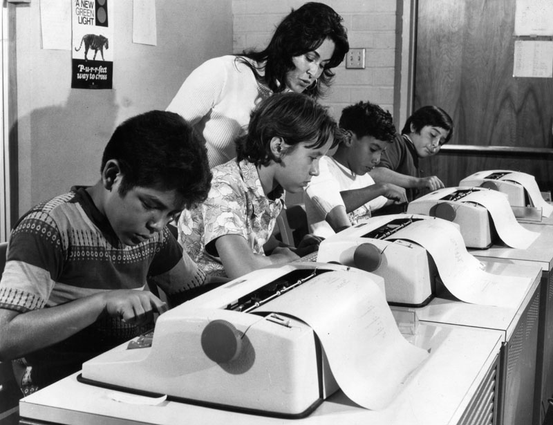 Black and white photo with a teacher standing behind four children and typrewriter like computer terminals.