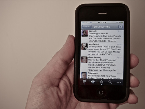 closeup of an iPhone displaying Twitter client, held by a white, male hand.
