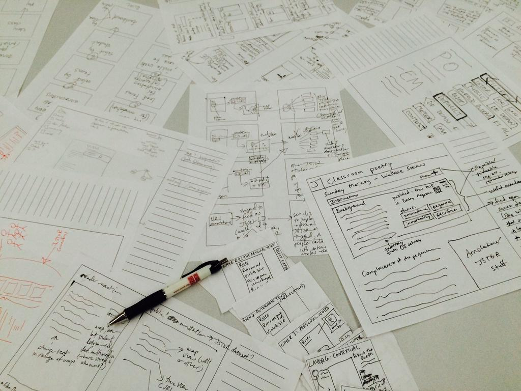 Sheets of paper with hand-drawn sketches of a web annotation interface, lying on a table.