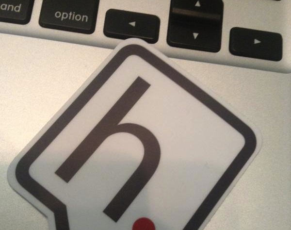 A sticker showing the hypothes.is logo--a black lower-case 'h' in a square speech bubble--on a Macbook keyboard