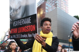 This image shows an African American woman protests on a city street. She stares off into the distance; her face reveals nothing. She is holding a sign that says hashtag say her name Kyam Livingston July 24th 2013 Brooklyn, New York.