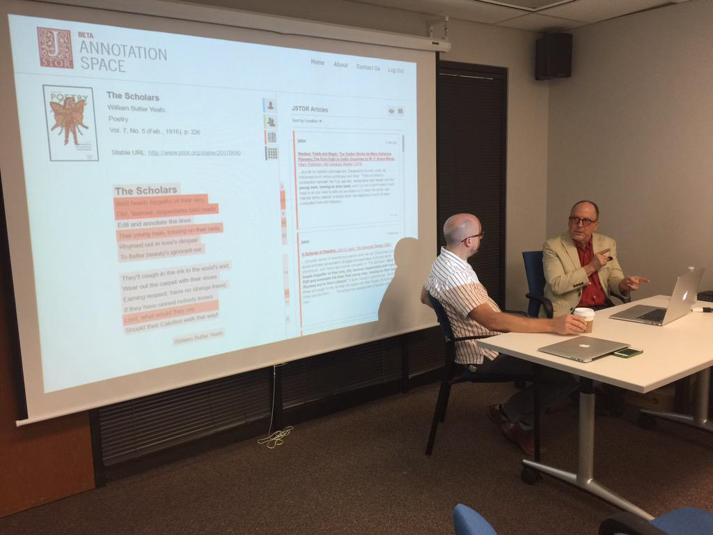 Two men in conversation over a laptop, sitting in front of a projector screen showing a poetry annotation screen.