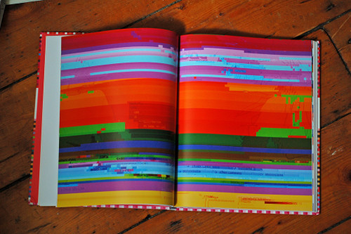 An open book in lying on a wooden floor. The pages show the bright color bands of computer screen displaying a visual glitch.