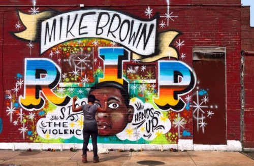 "This image features a mural to honor shooting victim Michael Brown. It reads ""MIKE BROWN. R. I. P. Stop the Violence. Hands Up."" In front of the mural, a young black woman stands with her back to the camera. Her hands are raised."