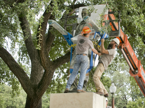 Image shows two men positioning a crane to remove the plastic-wrapped statue of Jefferson Davis.