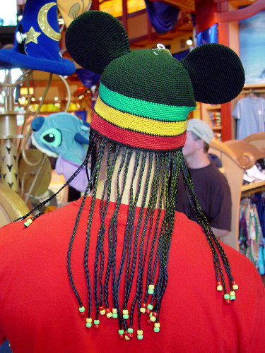 From-behind view of a white man in a Disney store. He is wearing a hat with Mickey Mouse ears, stripes in the African colors green, yellow and white, and fake black-haired braids dangling down his neck.