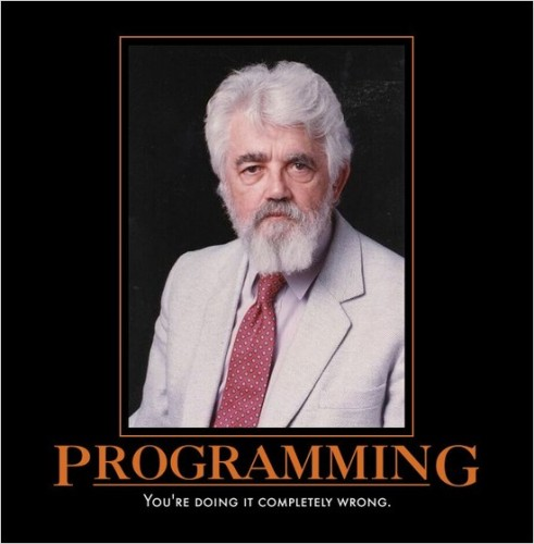 "A grey-haired man in a grey suit and red tie looking out from a black background directly at the viewer. The caption reads ""Programming: You're doing it completely wrong."""