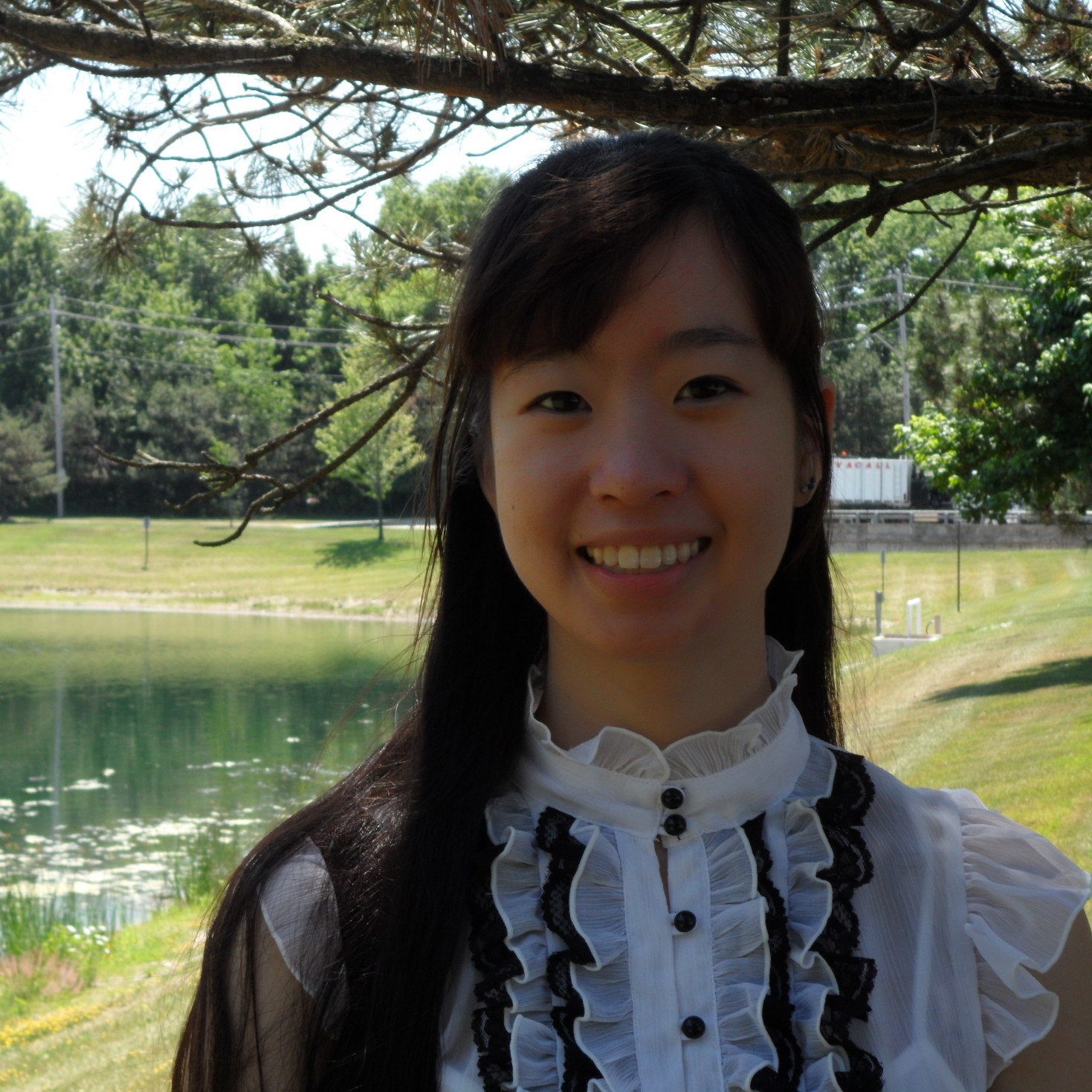 Photograph of DWRL staff member Lily Zhu, standing by a lake