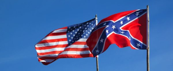 the american flag and the confederate flag flying at equal height. the confederate flag partially overlaps the american.