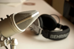 A close-up photograph of a studio microphone. The microphone extends into the left half of the frame. In the background on the right, and out of focus, is a set of Behringer headphones lying on a white table.