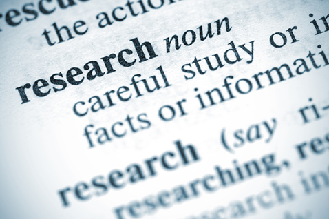 A close-up of a dictionary definition of research.