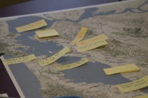 A close-up of a topographical map with a number of yellow sticky notes attached to it. The notes have different people's handwriting on them.