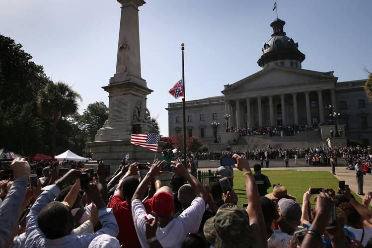 Image shows a crowd watching the Confederate Flag be lowered outside a building with columns.