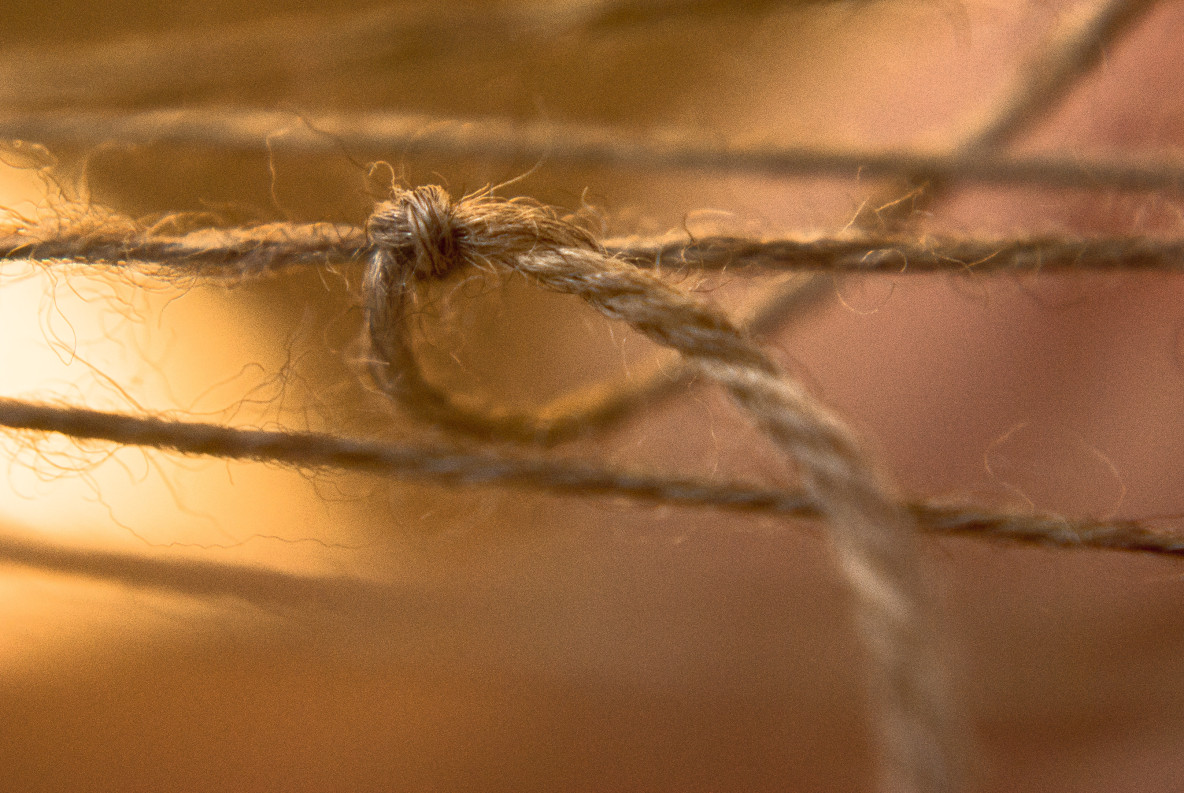 A knot tied in a piece of brown twine.