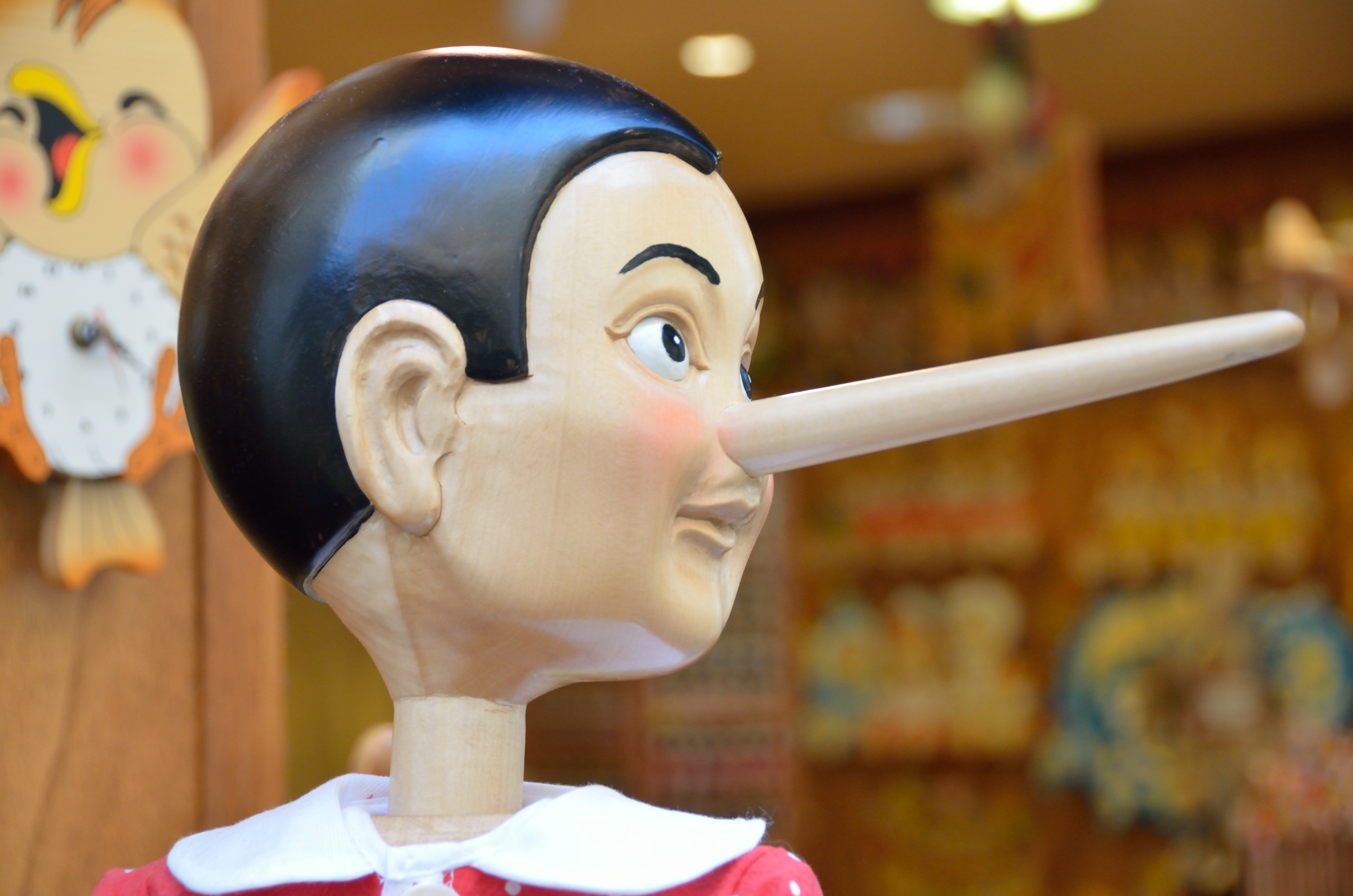 A wooden Pinocchio puppet, long nose pointing to the right.