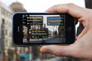 A hand is holding up a smartphone that shows an AR-app in use. The screen looks like the camera mode is on, but there are three translucent boxes overlaid on the streetview, which show the names of three locations on a German street that have free wifi, as well as their wifi's signal strength and the walking distance to each location.
