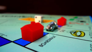 """The corner of a Monopoly gameboard showing the space """"Boardwalk,"""" which is a high value property in the game. The space also has a hotel on it, which indicates that it is a lucrative property. Behind the plastic, red hotel is a small metal car gamepiece."""