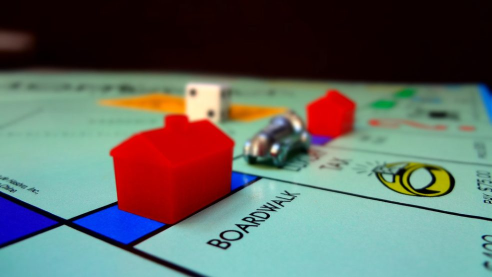 "The corner of a Monopoly gameboard showing the space ""Boardwalk,"" which is a high value property in the game. The space also has a hotel on it, which indicates that it is a lucrative property. Behind the plastic, red hotel is a small metal car gamepiece."