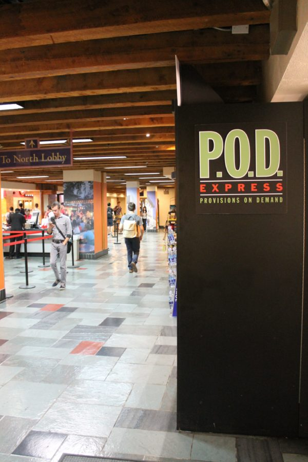 """Photo of Provisions On Demand food kiosk in the Texas Union building. Black box at right with """"P.O.D"""" label; students walking past on left"""