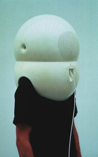 A picture of a man wearing a giant white device over his head. The device is plugged into something out of view, and the device looks extremely inconvenient and cumbersome. The image conveys a sense of devices taking their users hostage, or humans being inconvenienced by that which they designed for the sake of convenience