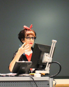 This is a picture of Avital Ronell in a speaking gesture with her right arm, spreading her four fingers and holding a blue pen with her thumb. She is standing in fron of two computer screens. Behind here is a dark wall. She is looking into the camera and is wearing black rectangular glasses. She has red lipstick and a red ribbon in her her. Her hair is mainly black, and she wears a black jacket with a white-red blouse.