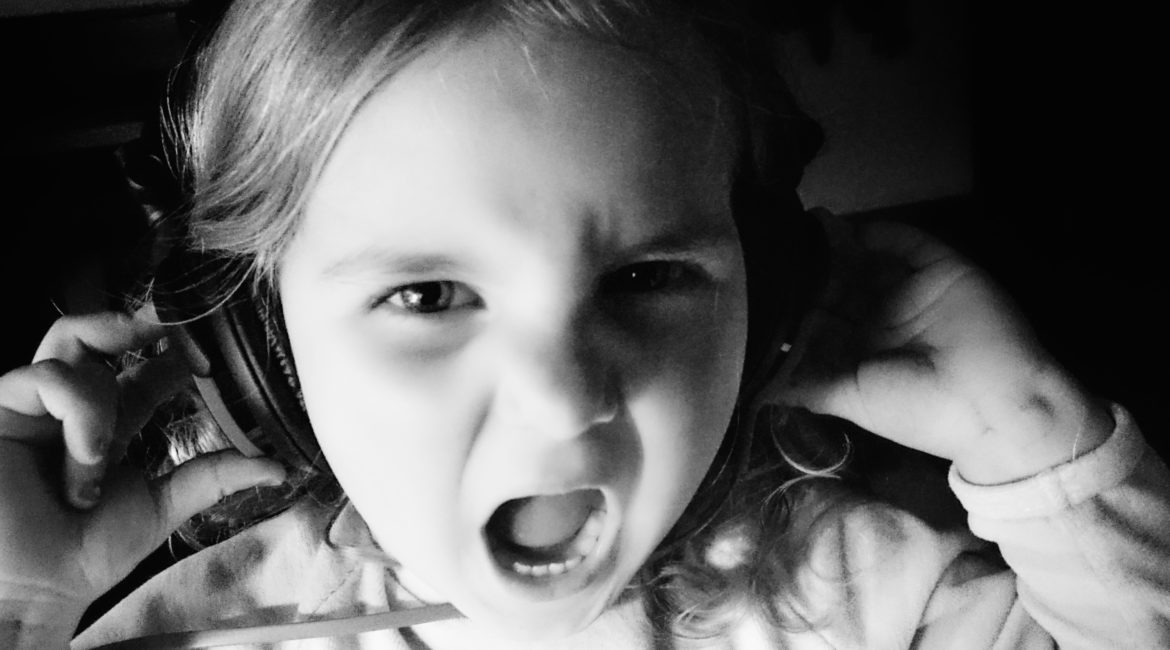 Black and white picture of a little girl wearing big headphones, looking like she's screaming.