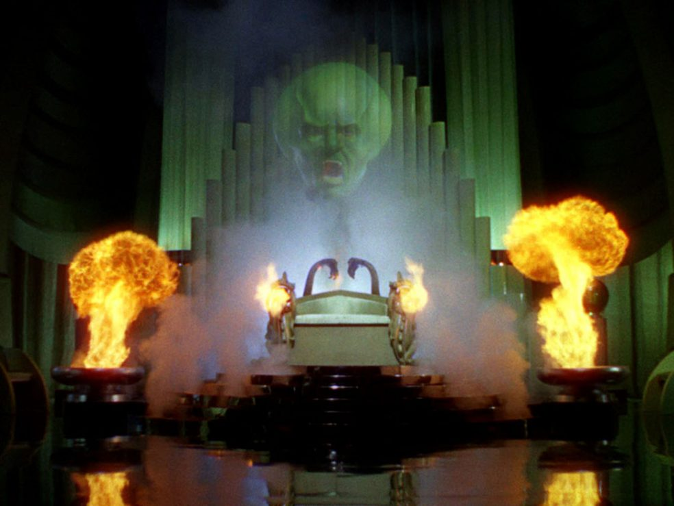 The image shows the intimidating, green, and translucent head of a man hovering in the air above some sort of altar in what could be a throne room. The man is shouting, and he has an enlarged cranium. Below the floating head is dense smoke. Partially encased by the smoke is a metalic scultupre with fire coming out of its sides toward the camera. At both the left and the right edges of the altar, fire erupts out of short but thick columns. The floor is black, but shiny and reflective. The back of the altar (behind the semi-transparent head) are tall narrow columns that resemble a massive church organ.