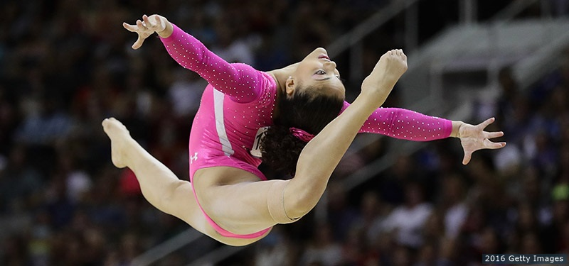 Laurie Hernandez again leaping on the balance beam. Photo focused entirely on her body and its form with the crowd blurred in the background and beam not included.