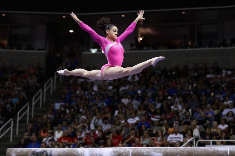 U.S.A. Olympic Gymnast Laurie Hernandez leaping on the balance beam. Photo shows her flying high above the beam and the crowds in the stands behind her.