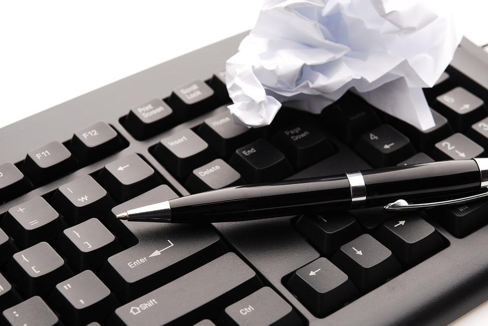 Close-up shot of a black keyboard on which rests a pen and a crumpled up piece of paper.
