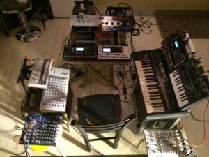 A single chair surrounded by a mass of electronic instruments. The image links to longer description.