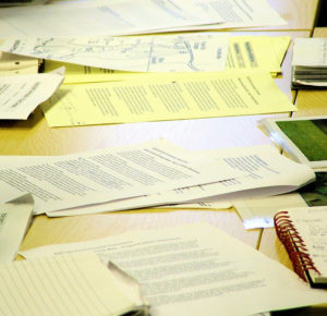 Wooden desk strewn with loose papers and spiral notebooks