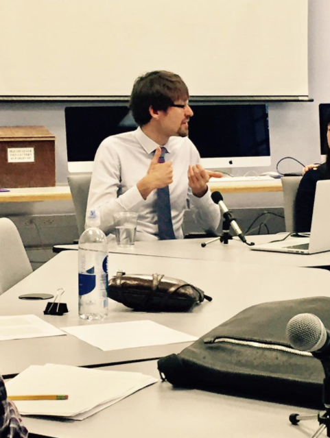 Picture of Dr. Jagoda, who has brown hair and glasses, and is sitting at a roundtable.