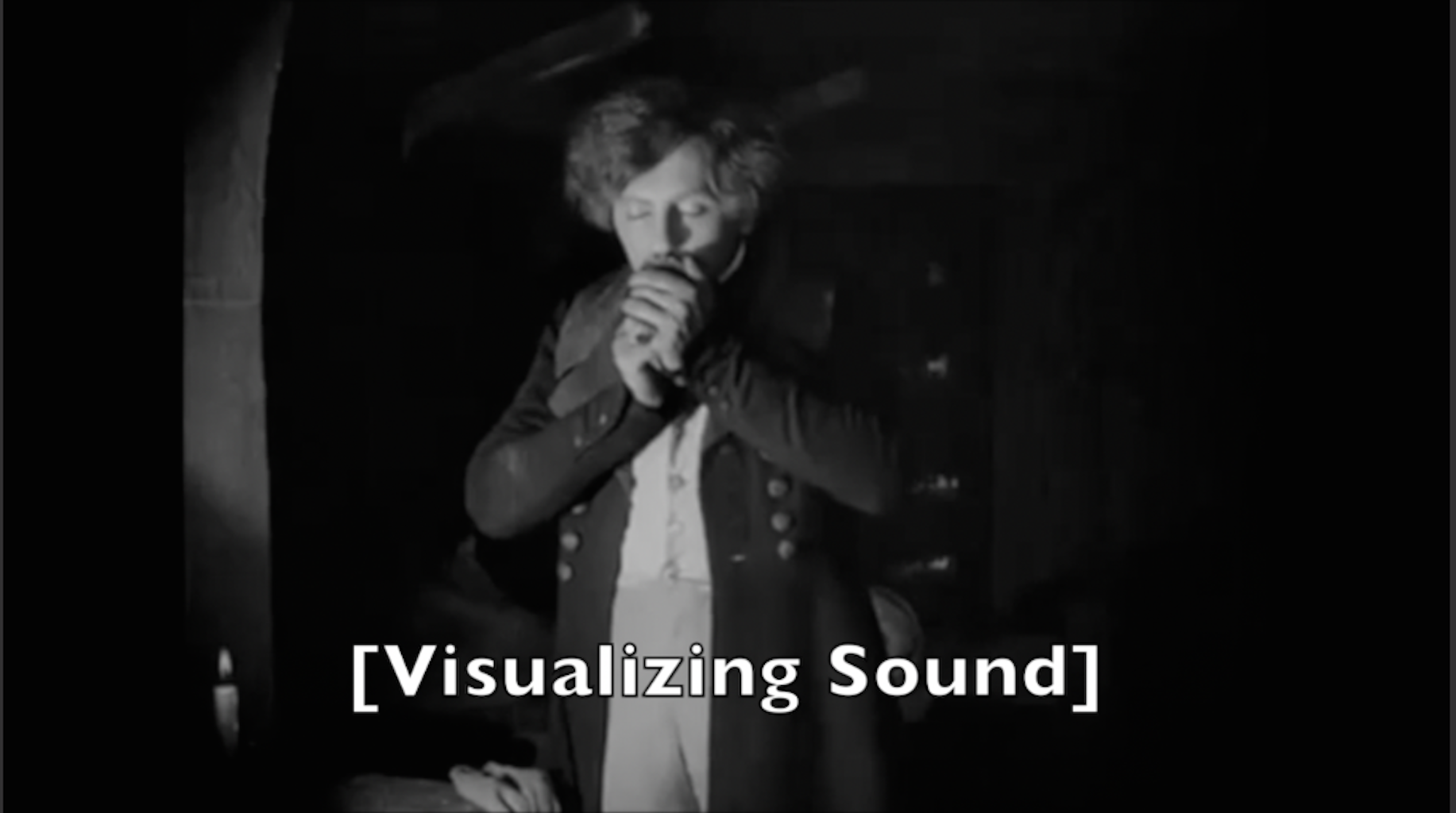 """Image of a man kissing something in his hands, with a the title """"Visualizing Sound"""" in brackets."""