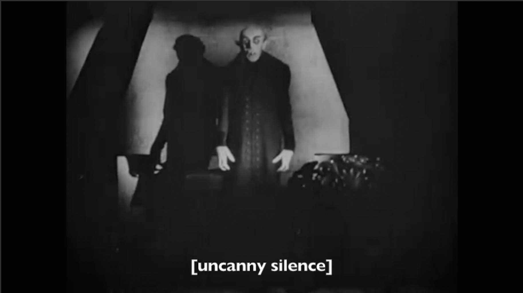 """Image of Nosferatu with a caption that reads """"uncanny silence"""" in brackets."""