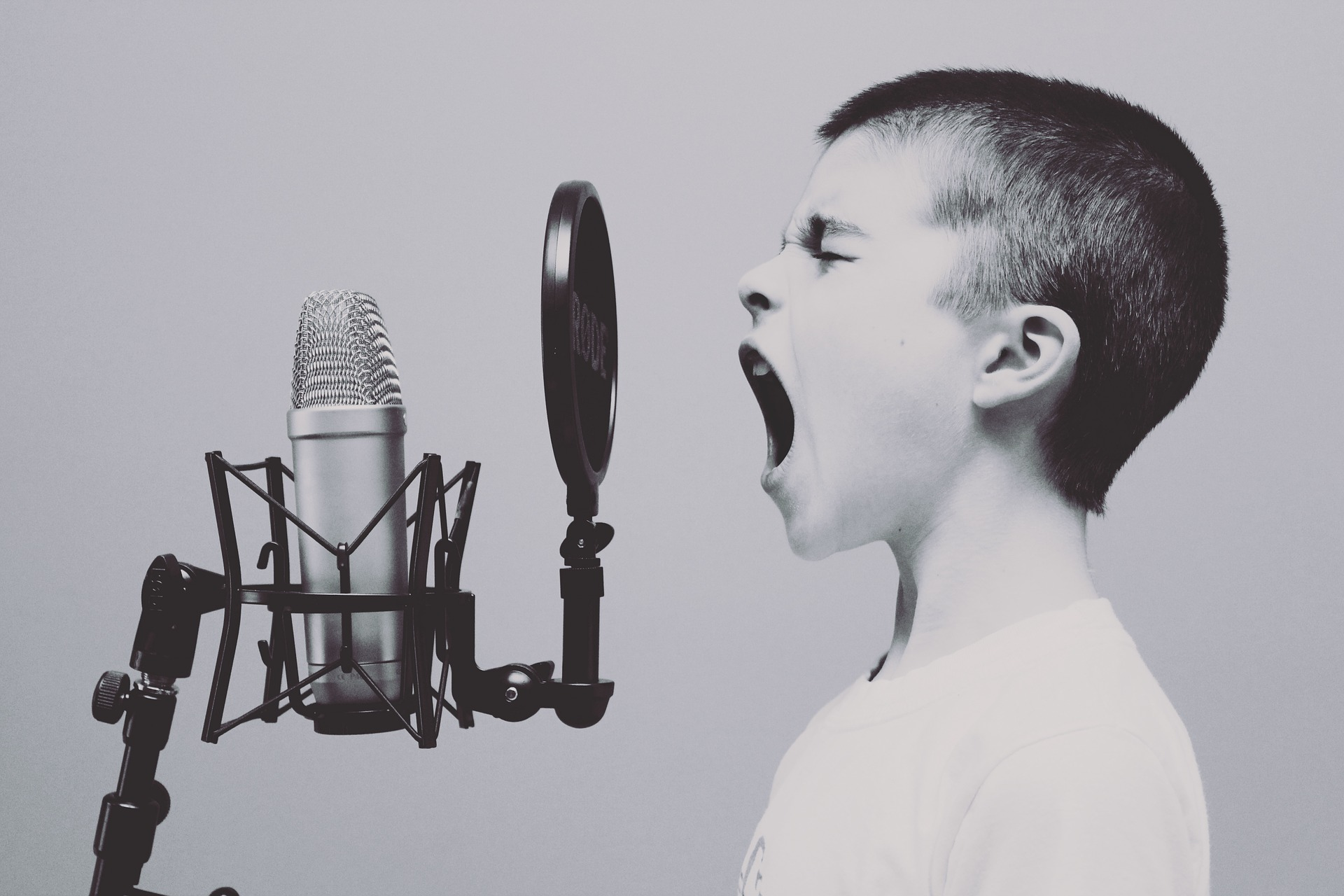 A young boy shouting into a microphone.