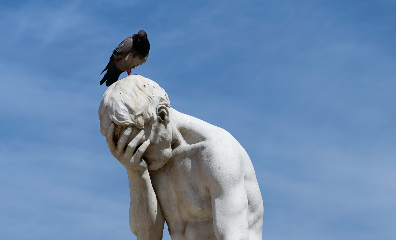 A white statue of Cain shows him with his head in his palm. A pigeon sits atop the statue's head. The statue is set in front of a bright blue sky.