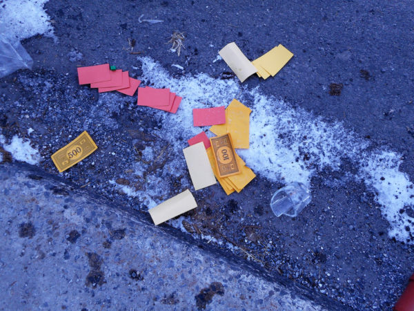 Monopoly money on the ground, ice and broken glass.