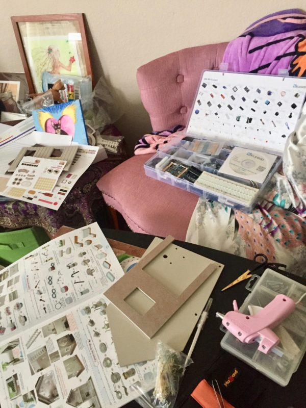 An Arduino computing kit sits atop a plush, pale pink chair in the background of the image. In the foreground, various supplies and instructions for a model home rest next to a pink glue gun on a black table.