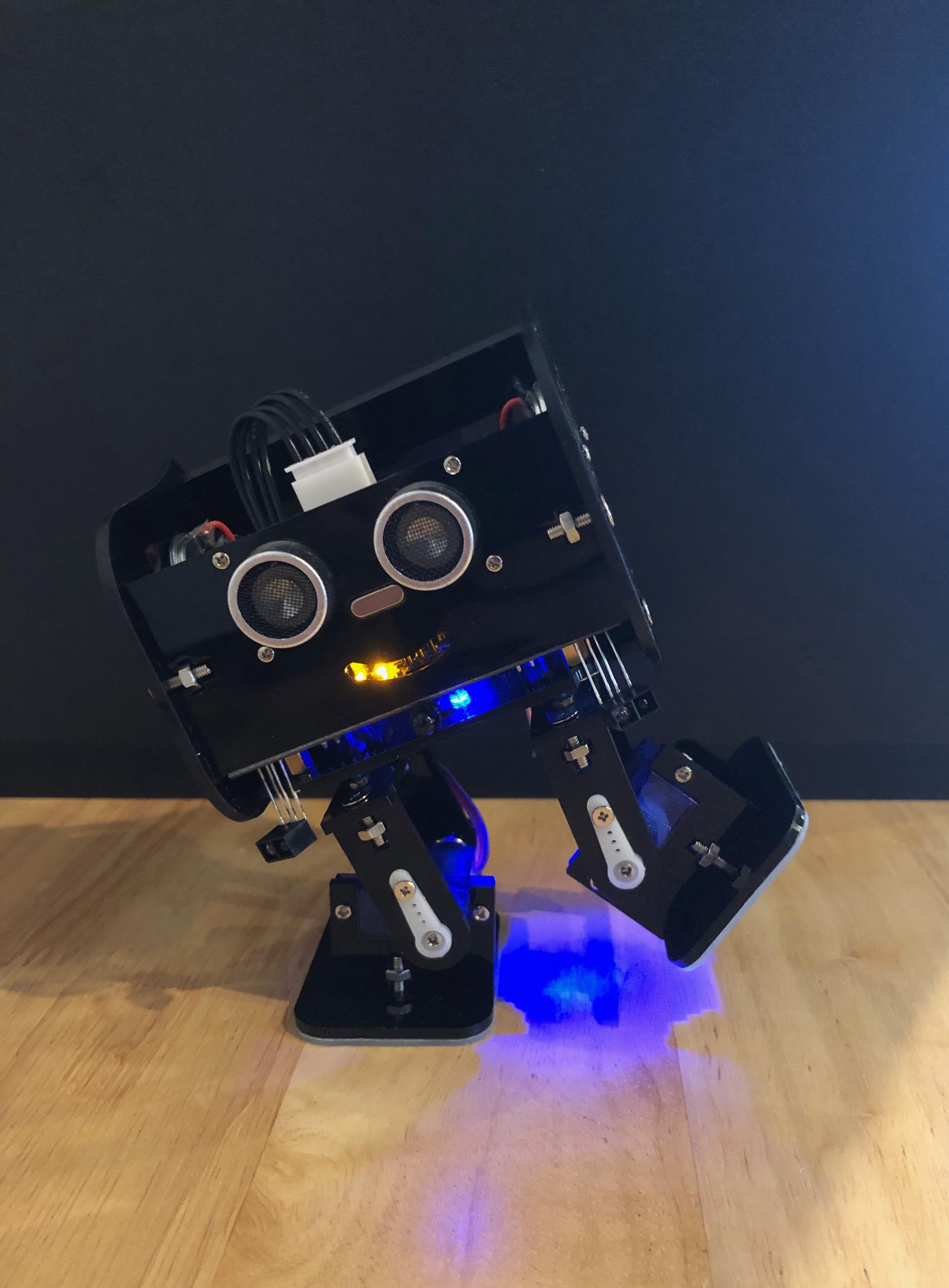 A Black, bipedal Arduino-based robot dancing