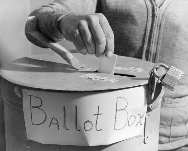 Hand dropping ballot in a locked ballot box